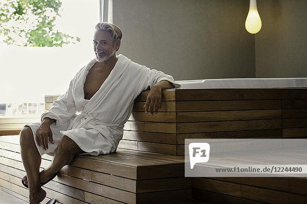 Mann im Bademantel entspannt im Saunaraum