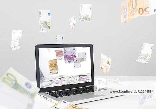 Online Einkaufen - Laptop und fliegende EURO-Scheine