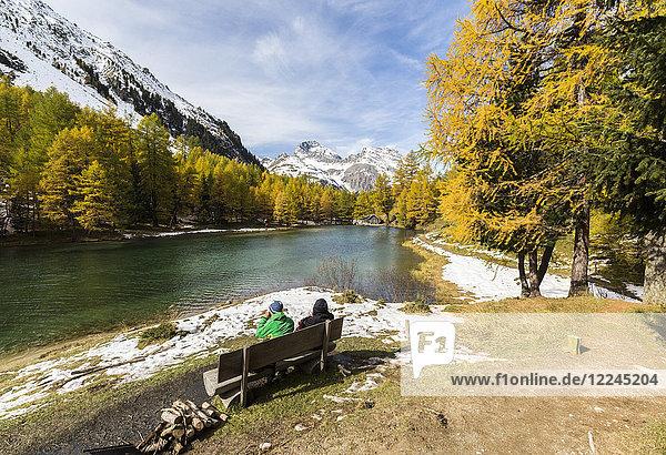 People on a bench on the shore of Lai da Palpuogna (Palpuognasee)  Bergun  Albula Pass  Canton of Graubunden (Grisons)  Switzerland  Europe