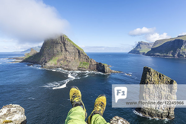 Man lays down on cliffs above the sea stacks of Drangarnir and Tindholmur islet  Vagar Island  Faroe Islands  Denmark  Europe