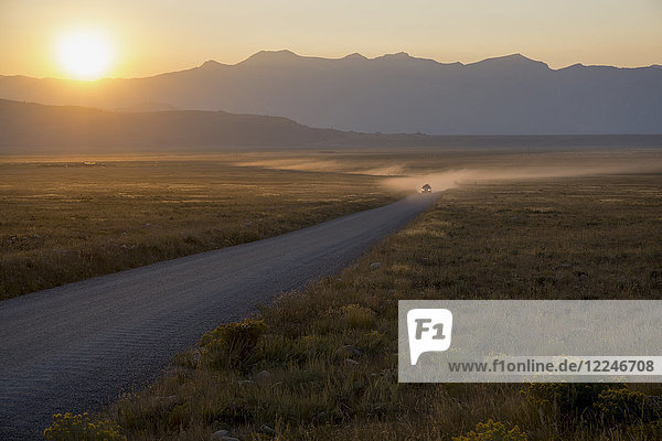 Car on dusty road at sunset  Grand Teton Park  Wyoming  United States of America  North America
