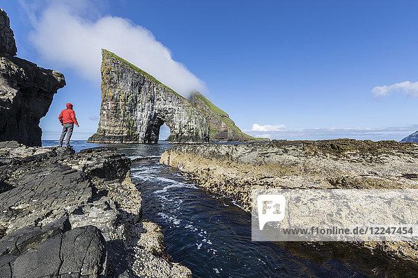 Man on cliffs looks towards the natural arch of Drangarnir rock  Vagar Island  Faroe Islands  Denmark  Europe