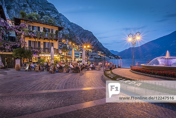 View of illuminated promenade at the port of Limone at dusk  Lake Garda  Lombardy  Italian Lakes  Italy  Europe