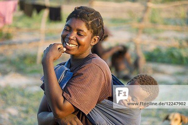 Lachende Tonga-Frau mit Kind auf dem Rücken  Lake Kariba  Sambia  Afrika