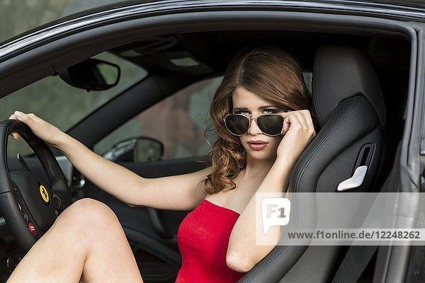 Junge Frau in Hotpants posiert in schwarzem Ferrari 458 Italia  Fashion  Lifestyle