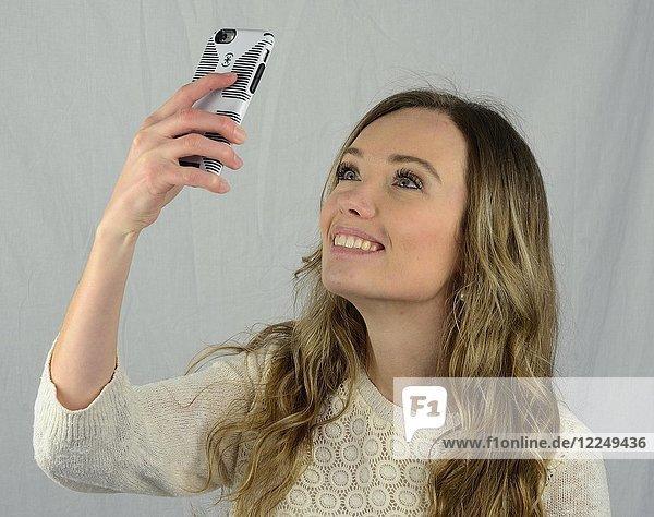 Junge Frau macht ein Selfie mit dem Handy  Lächeln