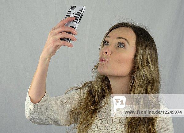 Junge Frau macht ein Selfie mit dem Handy  Kussmund
