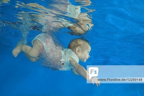 Säugling taucht in einem Schwimmbecken