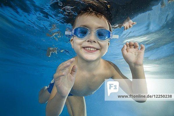 Kleiner Junge mit Schwimmbrille taucht in einem Schwimmbecken