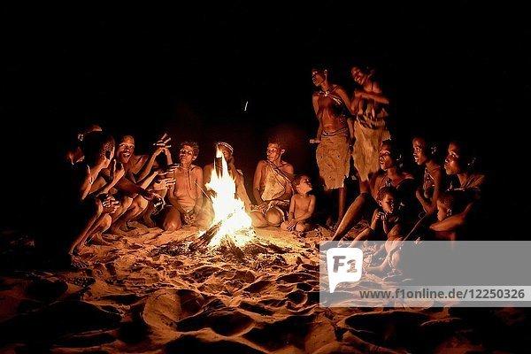 Buschleute der Ju/'Hoansi-San sitzen am Lagerfeuer  Dorf //Xa/oba  bei Tsumkwe  Otjozondjupa Region  Namibia  Afrika