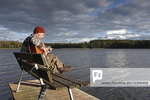 Man plays guitar on a boat landing stage at the lake  Mecklenburg Lake District  Mecklenburg-Western Pomerania  Germany  Europe