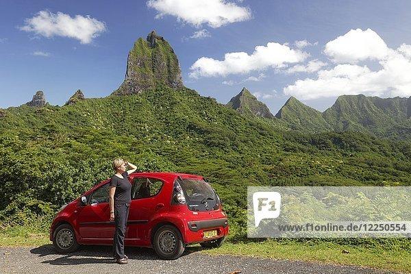 Frau mit rotem Auto am Belvedere Aussichtspunkt  grüner bewachsener Gebirgszug mit höchster Erhebung  Mont Tohiea  1207 m  Moorea  Gesellschaftsinseln  Inseln unter dem Winde  Französisch-Polynesien  Ozeanien