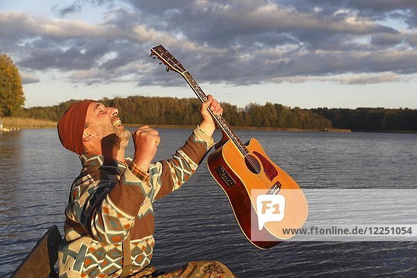 Man plays guitar on a boat landing stage at the lake and is pleased  Mecklenburg Lake District  Mecklenburg-Western Pomerania  Germany  Europe
