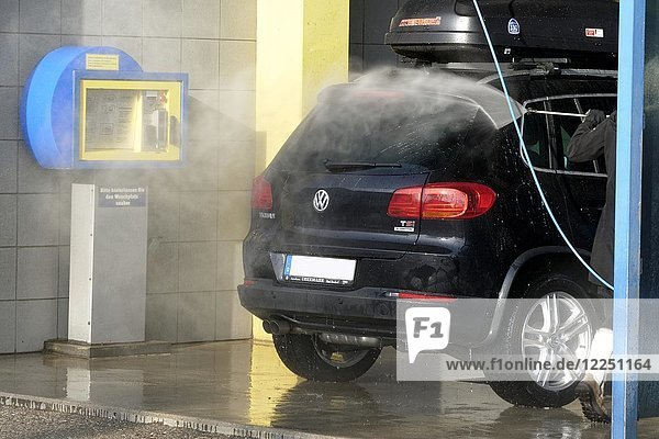 Cleaning car with water pressure hose  Upper Bavaria  Germany  Europe