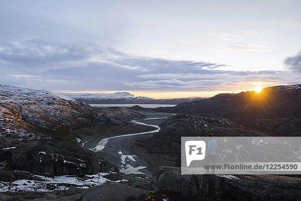 Mann steht auf Felsen und blickt in ein Flusstal in bergiger Landschaft  Sonnenuntergang  Westgrönland  Grönland  Nordamerika