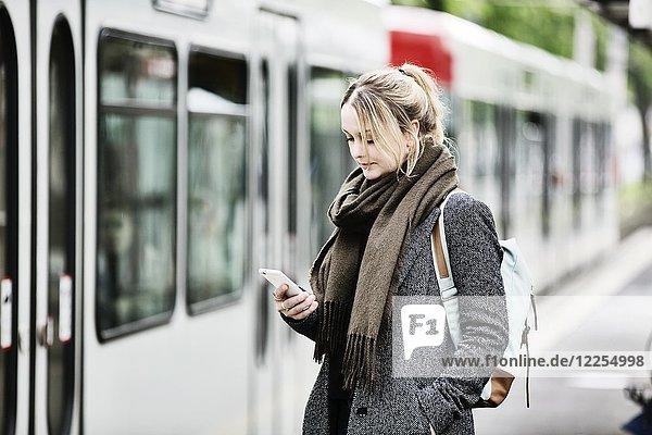 Junge Frau wartet mit ihrem Smartphone in der Hand an einer S-Bahn Haltestelle  Deutschland  Europa