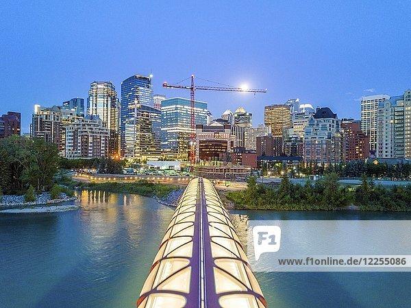 Calgary downtown at dusk with iluminated Peace Bridge and full moon  Alberta  Canada  North America