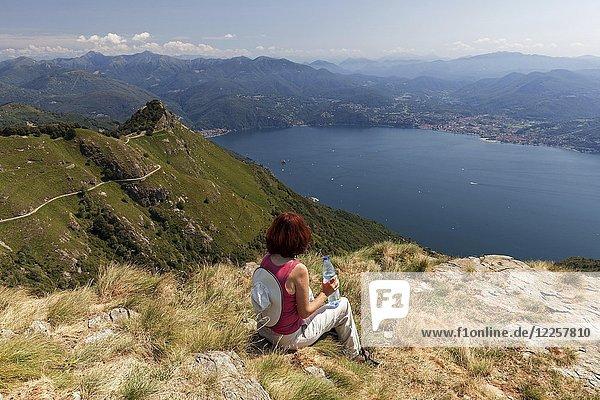 Wanderin blickt vom Morissolino auf den Lago Maggiore  links Gipfel Monte Morissolo  Cannero Riviera  Provinz Verbano-Cusio-Ossola  Region Piemont  Italien  Europa