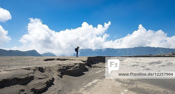 Junger Mann steht an einer Erdspalete und fotografiert  rauchender Vulkan Gunung Bromo  Mt. Batok  Mt. Kursi  Mt. Gunung Semeru  Tengger Caldera  Nationalpark Bromo-Tengger-Semeru  Java  Indonesien  Asien