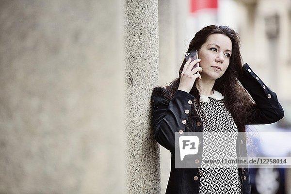 Junge Frau mit Retro-Kleid telefoniert mit ihrem Smartphone