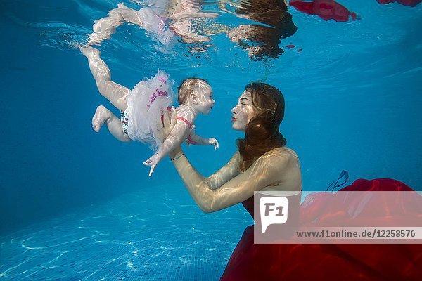 Schöne junge Frau in rotem Kleid mit Baby posiert unter Wasser im Pool  Ukraine  Europa