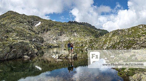 Wanderer-Paar steht auf einem Stein in einem kleinen See  Klafferkessel  Schladminger Höhenweg  Schladminger Tauern  Schladming  Steiermark  Österreich  Europa