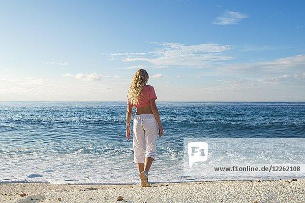 Junge Frau geht zur Brandung am Sandstrand  Fuvahmulah Island  Indischer Ozean  Malediven  Asien