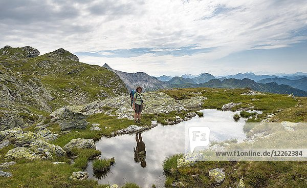 Wanderin spiegelt sich in einem kleinen See  Schladminger Höhenweg  Schladminger Tauern  Schladming  Steiermark  Österreich  Europa