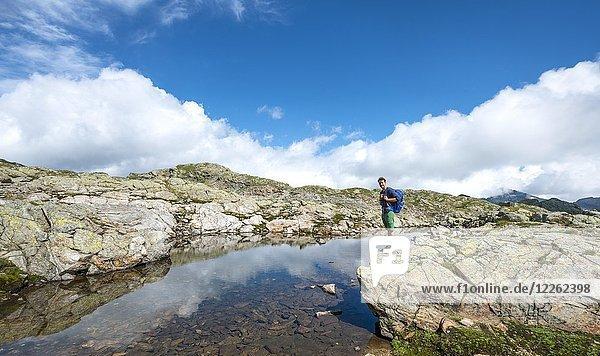 Wanderer an einem kleinen See  Klafferkessel  Schladminger Höhenweg  Schladminger Tauern  Schladming  Steiermark  Österreich  Europa