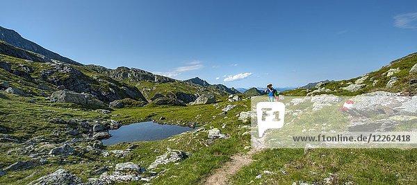 Hiker stehr at a small lake and photographed  Schladminger Höhenweg  Schladminger Tauern  Schladming  Steiermark  Austria  Europe