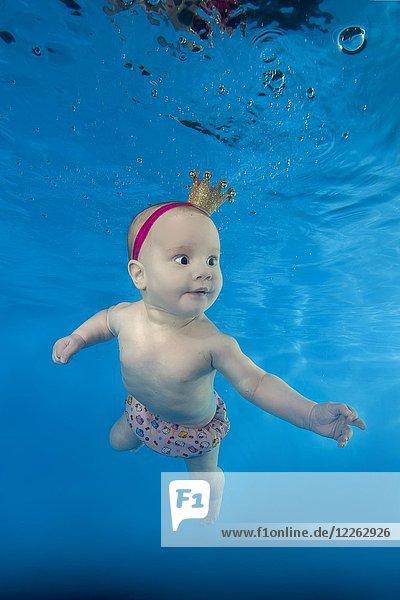 Ein kleines Mädchen mit einer Krone schwimmt unter Wasser im Pool  Ukraine  Europa