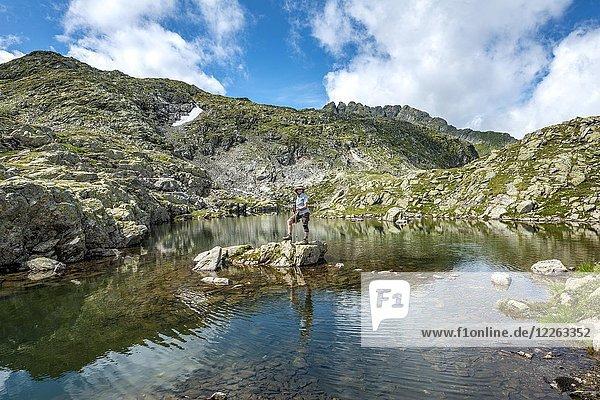 Wanderin auf einem Stein in einem kleinen See  Klafferkessel  Schladminger Höhenweg  Schladminger Tauern  Schladming  Steiermark  Österreich  Europa Wanderin auf einem Stein in einem kleinen See, Klafferkessel, Schladminger Höhenweg, Schladminger Tauern, Schladming, Steiermark, Österreich, Europa