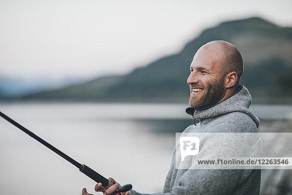 Kanada  British Columbia  glücklicher Mann beim Angeln am Kinbasket Lake