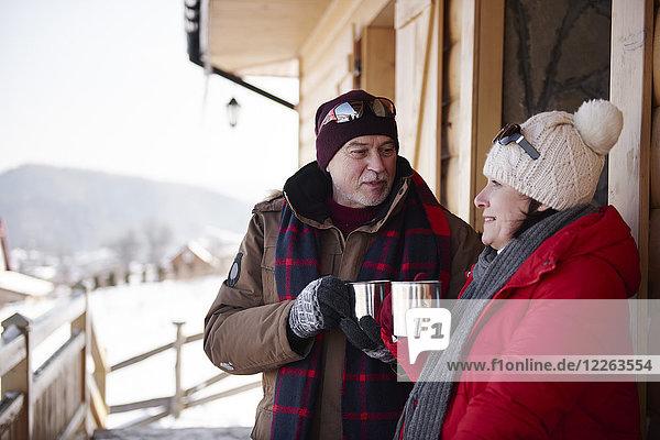 Ein reifes Paar mit heißen Getränken im Winter auf der Almhütte