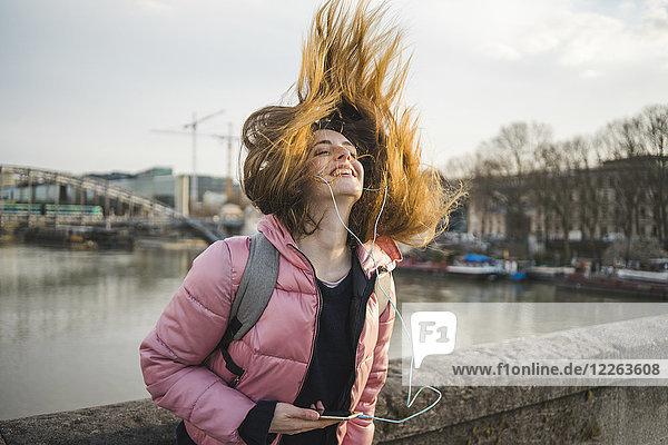 Paris  Frankreich  fröhliche junge Frau  die Musik mit Kopfhörern und Smartphone hört.
