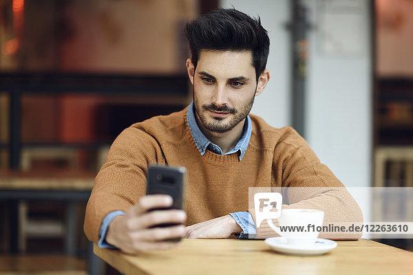 Porträt eines jungen Mannes  der mit dem Handy in einem Café sitzt.