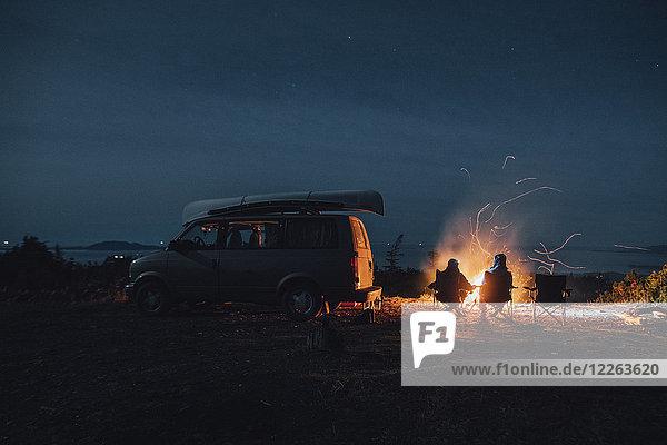 Kanada  British Columbia  Prinz Rupert  zwei Männer sitzen nachts am Lagerfeuer im Minivan.