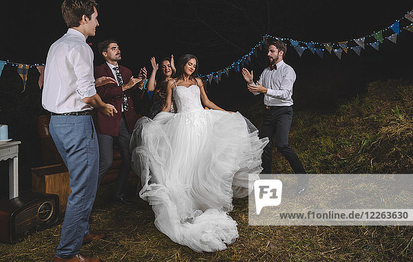 Happy bride dancing and having fun while her friends clapping on a night field party