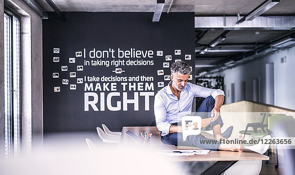 Der reife Geschäftsmann sitzt barfuss auf dem Schreibtisch im Büro mit Tablette