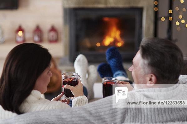 Erwachsenes Paar mit heißen Getränken im Wohnzimmer am Kamin