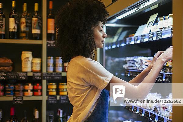 Frau arbeitet im Regal eines Ladens