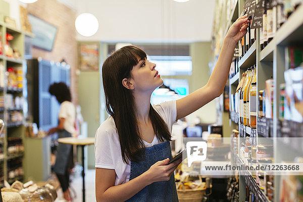 Frau mit Tablette im Ladenregal