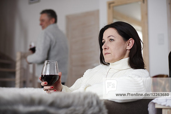Serious mature woman with glass of wine and man in background