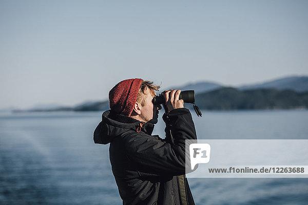 Kanada  Britisch-Kolumbien  Mann schaut durchs Fernglas an der Küste.
