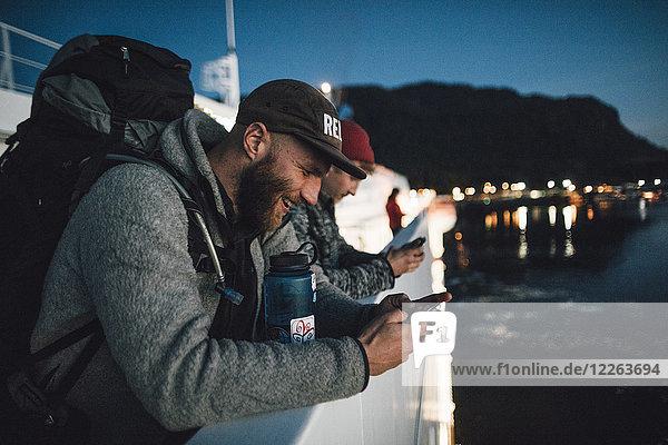 Kanada  British Columbia  zwei Männer auf einem Boot  die nachts Mobiltelefone benutzen.