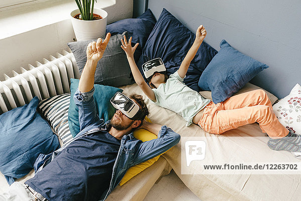 Vater und Sohn mit VR-Brille zu Hause liegend