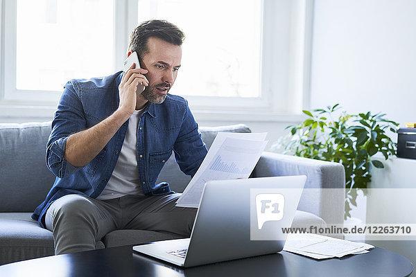 Seriöser Mann mit Dokumenten und Laptop auf dem Sofa  der auf dem Handy spricht