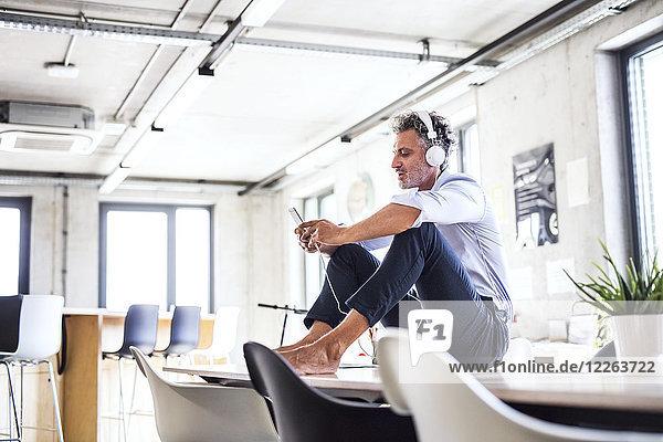 Geschäftsmann mit Smartphone und Kopfhörer  der barfuß auf dem Schreibtisch im Büro sitzt