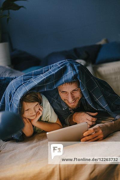 Glücklicher Vater und Sohn sehen sich einen Film unter der Decke an.