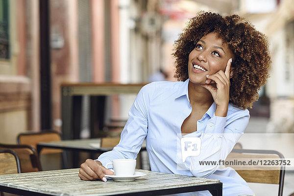 Lächelnde Frau mit Afro-Frisur sitzend im Outdoor-Café